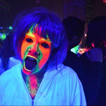 Frau mit Neon geschminktem Gesicht und aufgerissenem Mund in Schwarzlicht