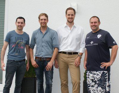 Foto von vier Männern nebeneinander aufgestellt vor einer weißen Mauer