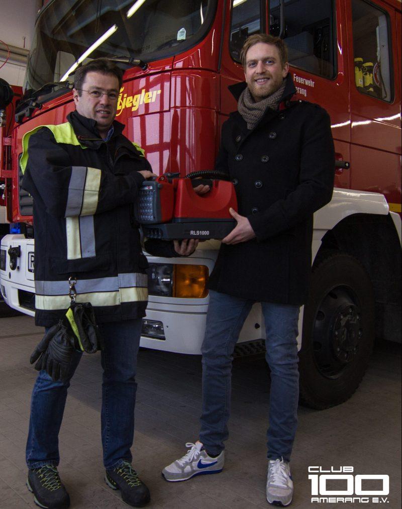 Ein Feuerwehrmann bekommt vor einem Feuerwehrauto von einem Zivilisten ein Lampe überreicht