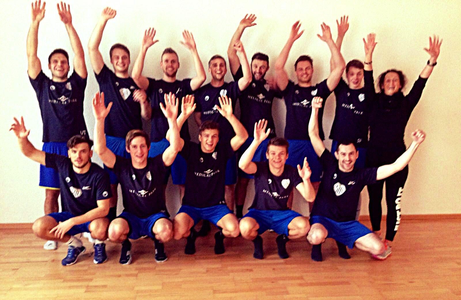 Fußballmannschaft auf Laminatboden vor weißer Wand aufgestellt