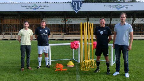 Vier Personen auf einem Fußballplatz mit Trainingsequipment