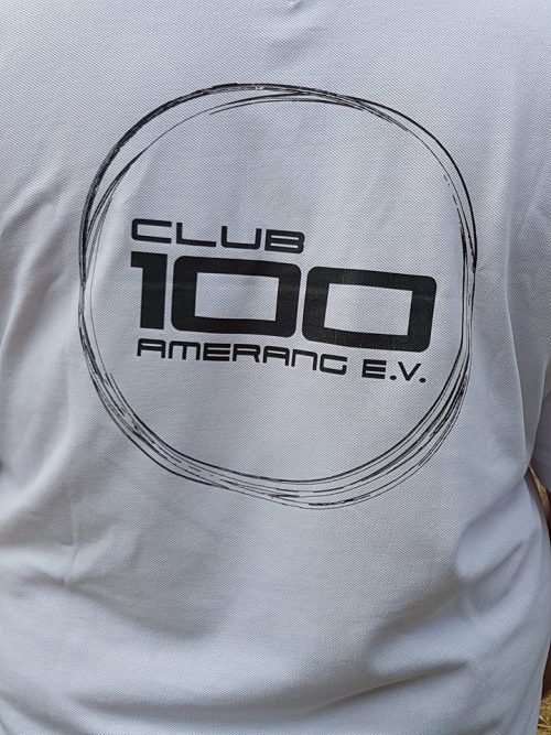 "Logo ""Club 100 Amerang e.V."" in schwarz auf weißem T-Shirt"