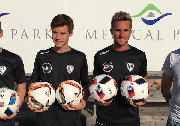 Drei Fußballspieler mit jeweils zwei Bällen in der Hand und ein Betreuer rechts daneben