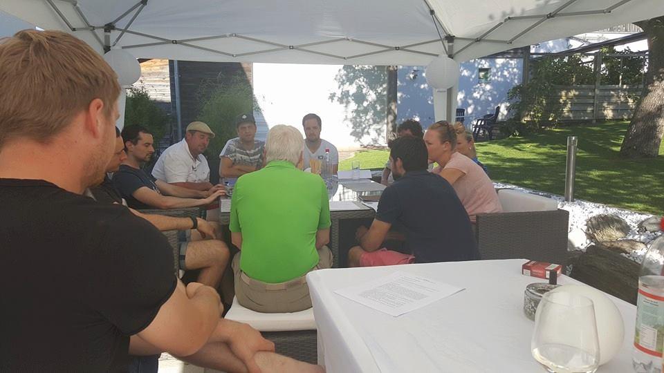 Menschengruppe diskutiert an einem großen Tisch